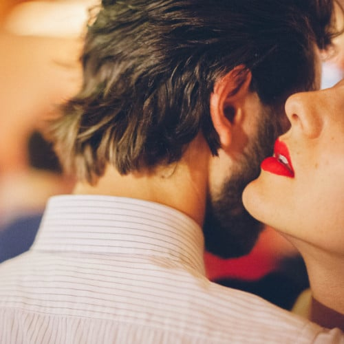 Woman whispers in man's ear