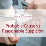 Featured Image for a blog about probable cause vs reasonable suspicion. Image shows a mans hands being handcuffed by a police officer.